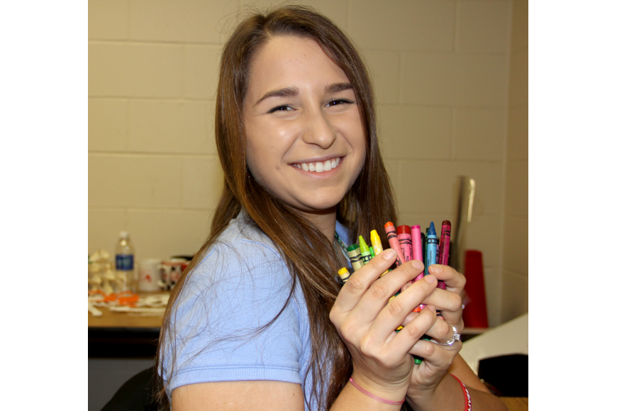 Bree Barron, a sophomore at Flagler Palm Coast High School, holds a handful of donated crayons to be used in her Community Problem Solving project, No crayon left behind. Photo Jacque Estes