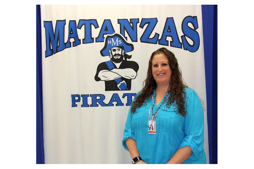 Michelle Czarnecki stands in front of the Pirate banner  her government class uses for video morning annoucements. Photo Jacque Estes