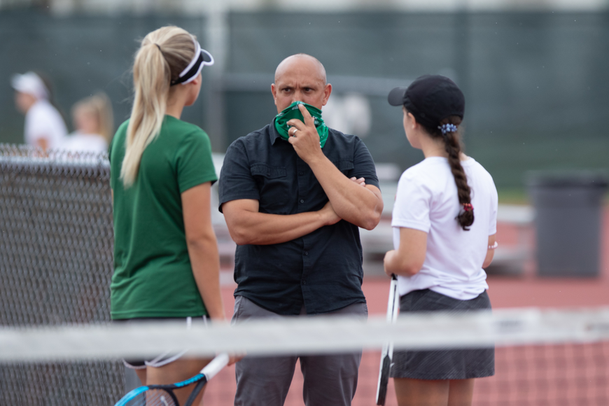 Coach Javier Bevacqua speaks with the FPC #1 doubles team at Tuesdays Regional match against Nease High School.