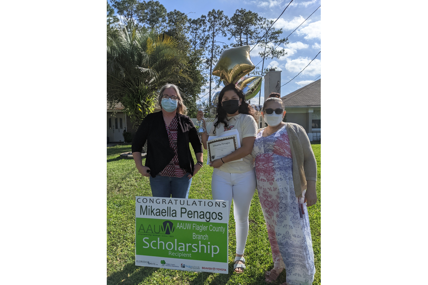 Haydee Bernal (white mask) and Terri Smith (blue mask), AAUW Flagler Scholarship Committee members, with Mikaella Penagos, FPCHS senior, and scholarship recipient. Courtesy photo
