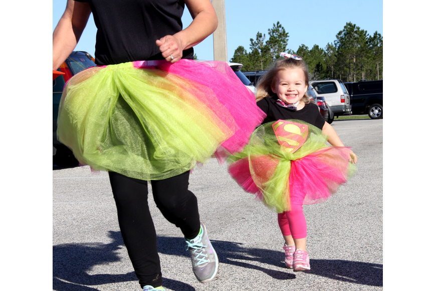 Rayna Ertel hangs onto her mom'       s tutu at the Bobcat 5K. Photo by Jacque Estes