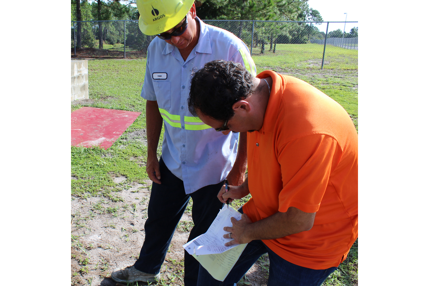 Jason DeLorenzo of the Flagler County Home Builders, signs off for concrete delivered by Todd Deuter of Argos Concrete. The supplies being used by the Matanzas High School construction tech class have been donated. Photo by Jacque Estes