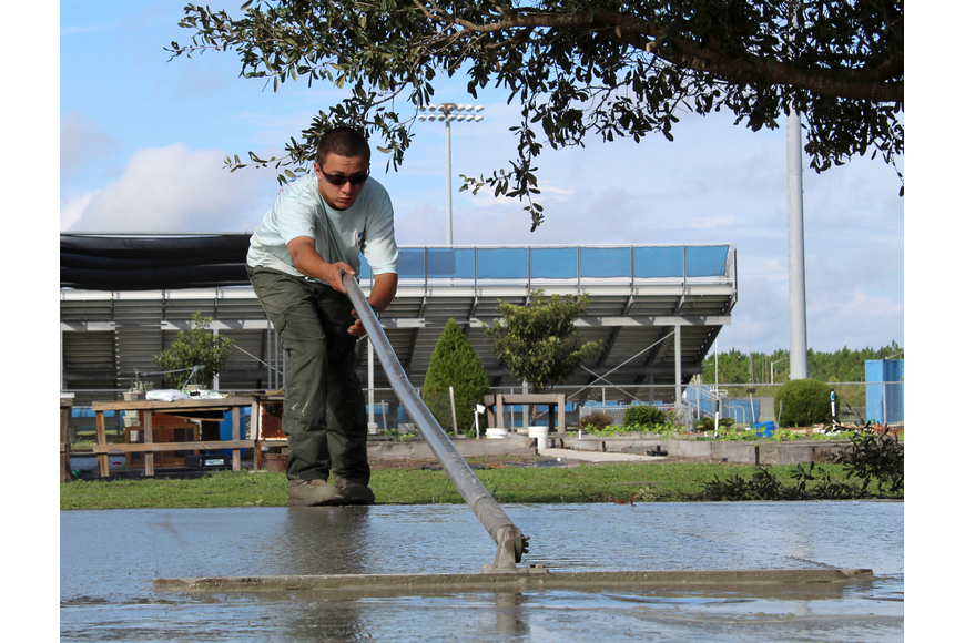 Julian Gomez smooths recently poured concrete at Matanzas High School for his construction tech class. Photo by Jacque Estes