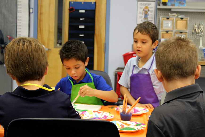 Enzo McGover (green smock) and Maksim Smolik (purple smock) sit and paint with Chris Asseo and Jack Rossheim (backs to the camera) during class at Belle Terre Elementary. Photo by Jacque Estes