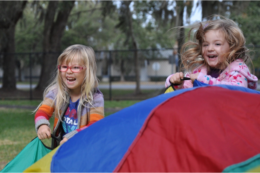 Hadassah Toro and Lily Whaley participate in a parachute game at the picnic.