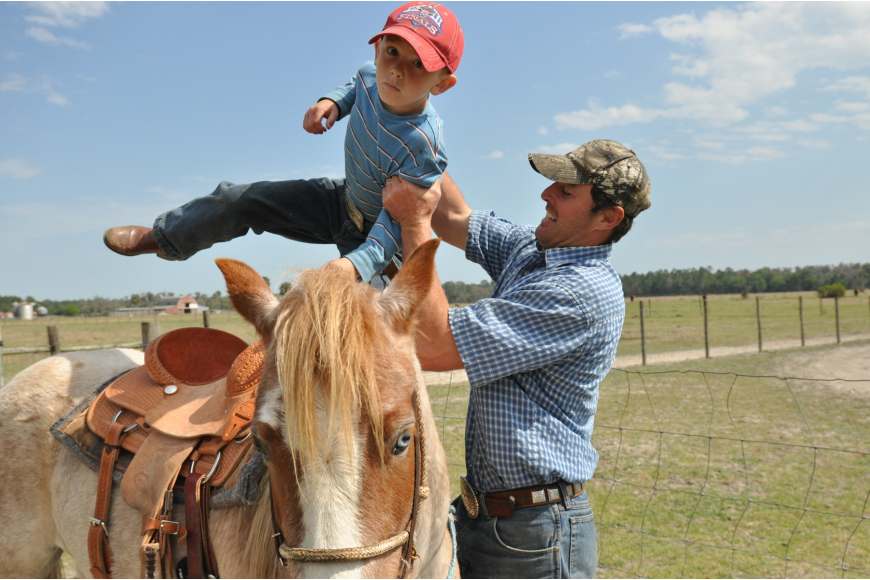 Ramzi Hughes helps his oldest son Ramzi on a horse before rounding up cattle to practice steer roping for Cracker Day.