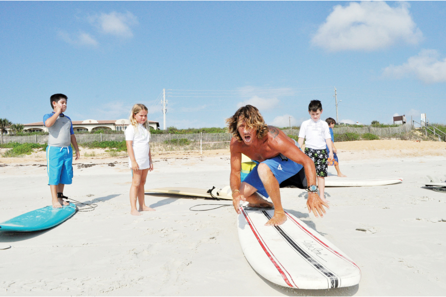 Jamie Ridgewell, of Sully's Surf and Skate, in Flagler Beach, demonstrates the proper pop-up technique to surfing hopefuls at the North Beach Surf Camp.