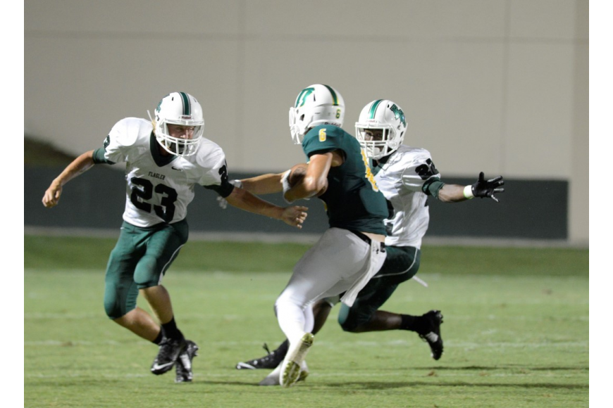 Alexander Folk (23) and Ladale Batson (22) corral DeLand wide receiver Charles Nordman. (Photo by Steven Libby)