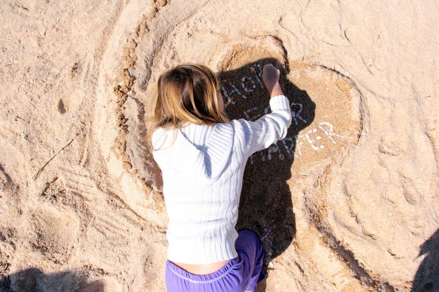 Riley Eddy puts the finishing touches on her sand sculpture of an octopus.