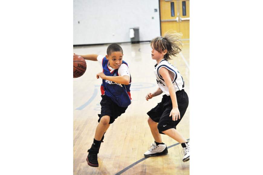 Jamaris Grey sneaks past Logan Stover during the U12 Police Athletic League basketball championship game.