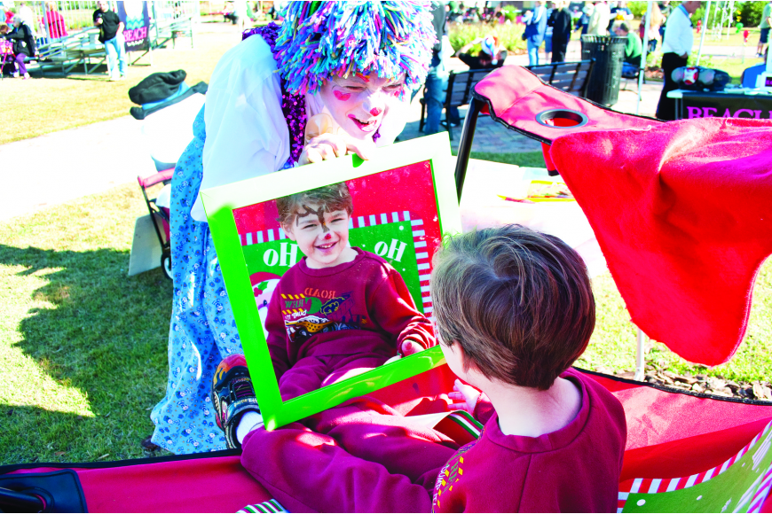 Cappy the Clown holds the mirror for Tony Tucci to view his Rudolf the Reindeer face painting Saturday, Dec. 11, at the Holiday Fantasy Fest, in Town Center.